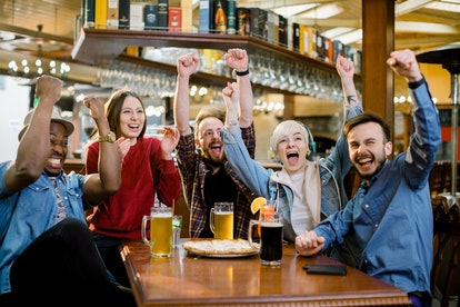 Excited diverse friends football fans celebrating victory goal score watching game online on tv in c...