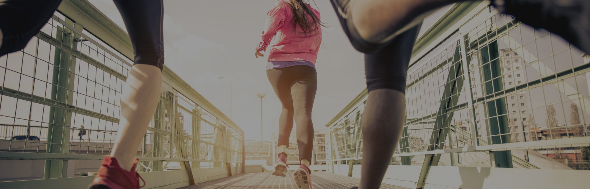 Three runners sprinting outdoors - Sportive people training in a urban area, healthy lifestyle and sport concepts