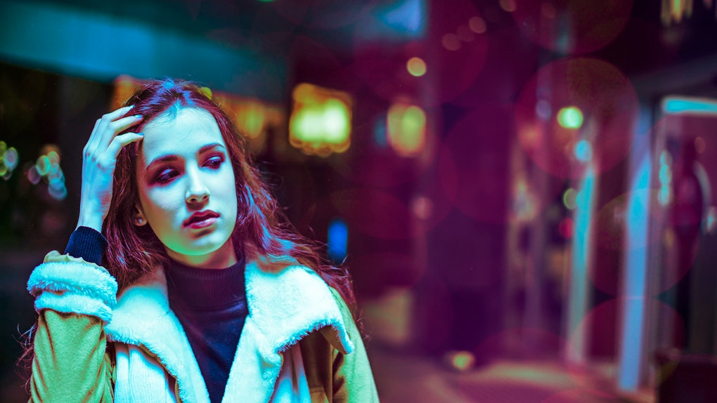 Night in the city, beautiful woman among red and blue neon lights. Sexy young beauty woman posing over night city dramatic violet and purple neon illuminated street background