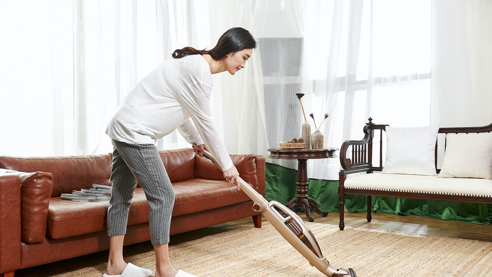 Young asian woman use wireless vacuum cleaner to clean