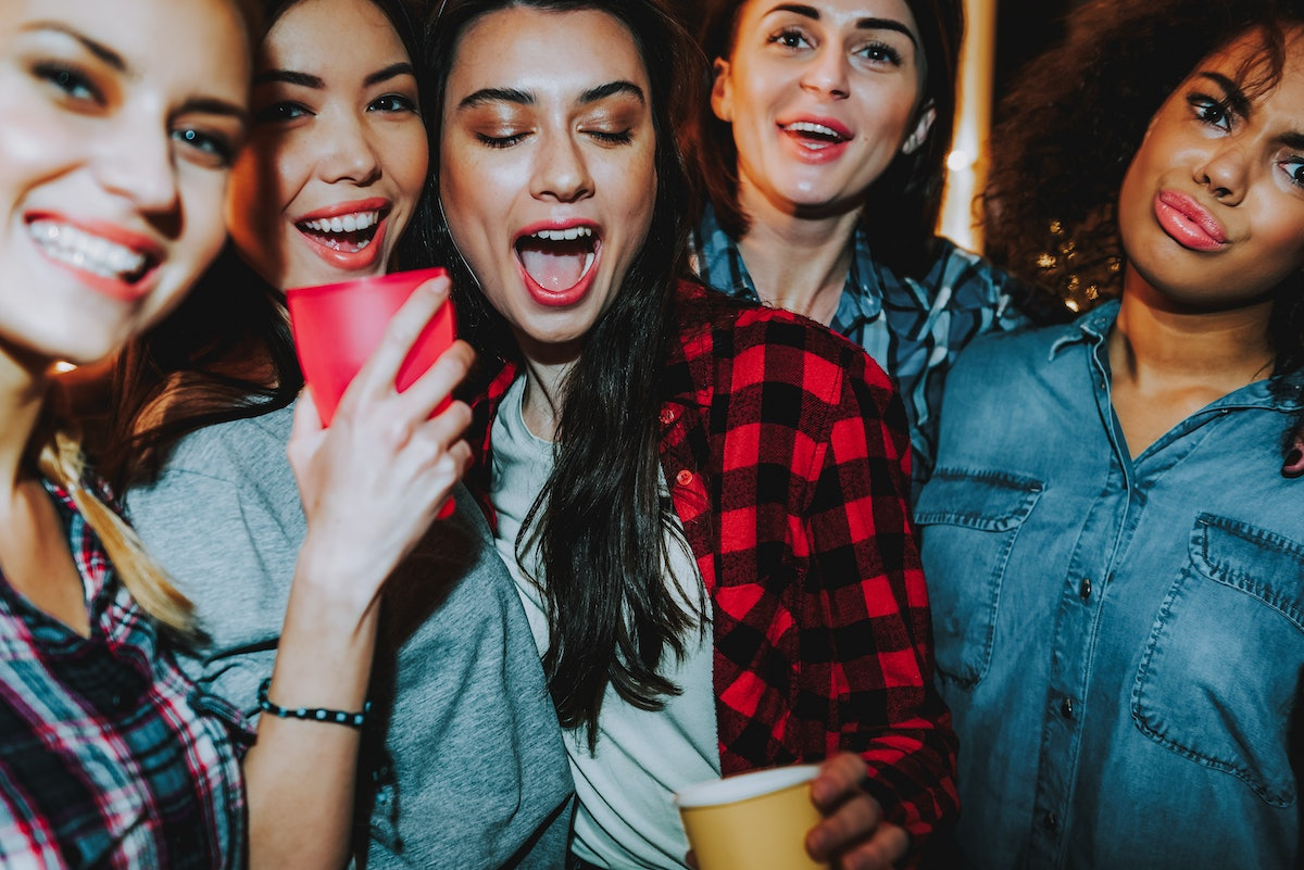 A group of women smile and pose for a picture at a party.