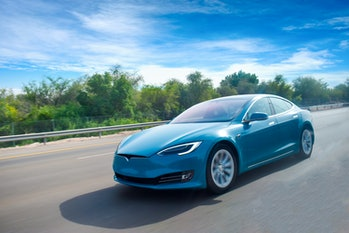 An electric car cruising on the highway,bluish sky and beautiful climate.green energy concept.