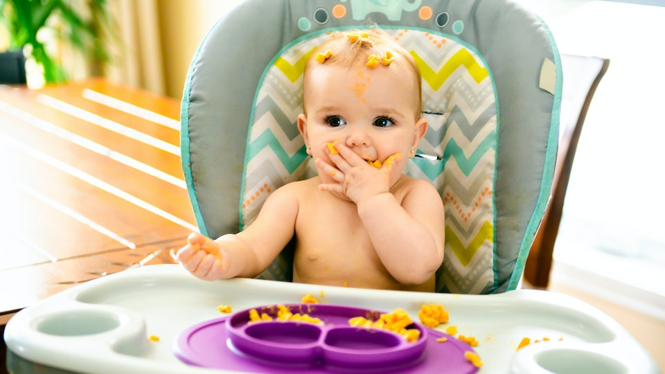 Little baby eating her dinner and making a mess