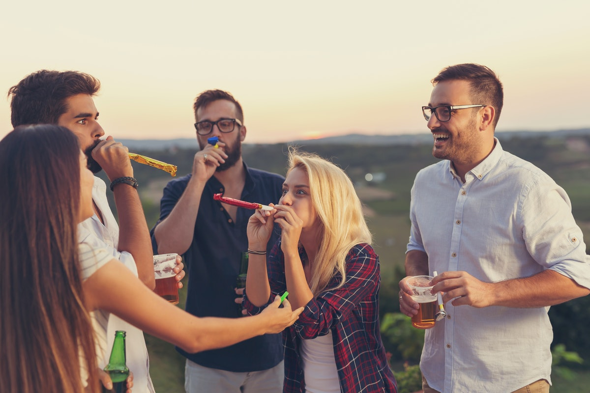 A group of friends have fun while blowing party whistles and drinking beer outside.