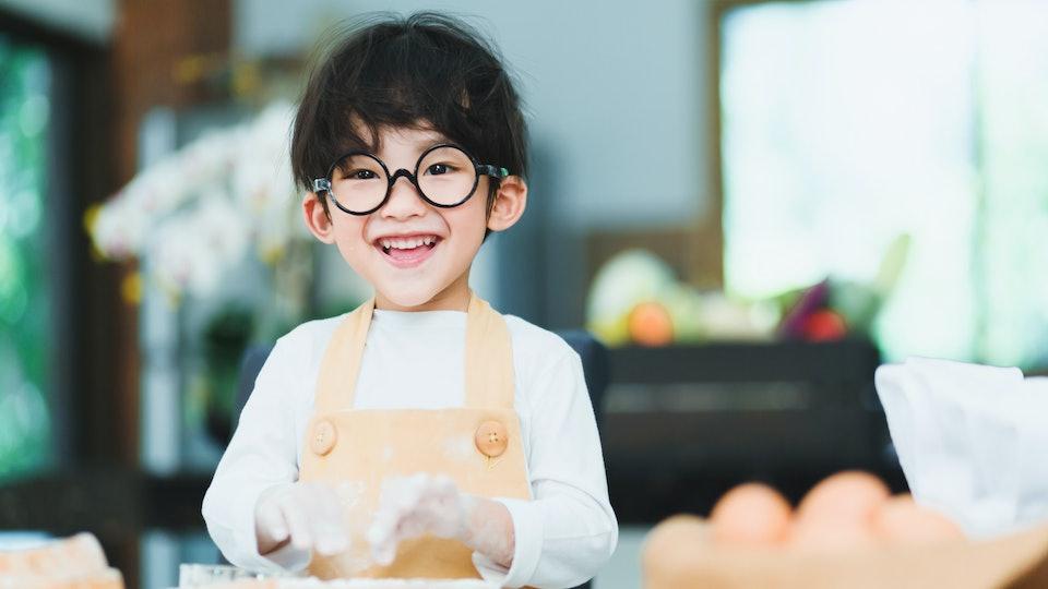 a little boy making breakfast