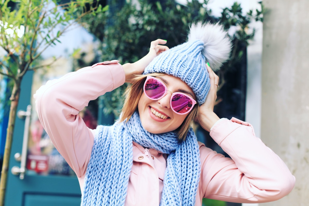 Girl in Winter Clothes in the City Street. Woman in Knitted Sweater, Sunglasses, Beanie and Scarf in the Street