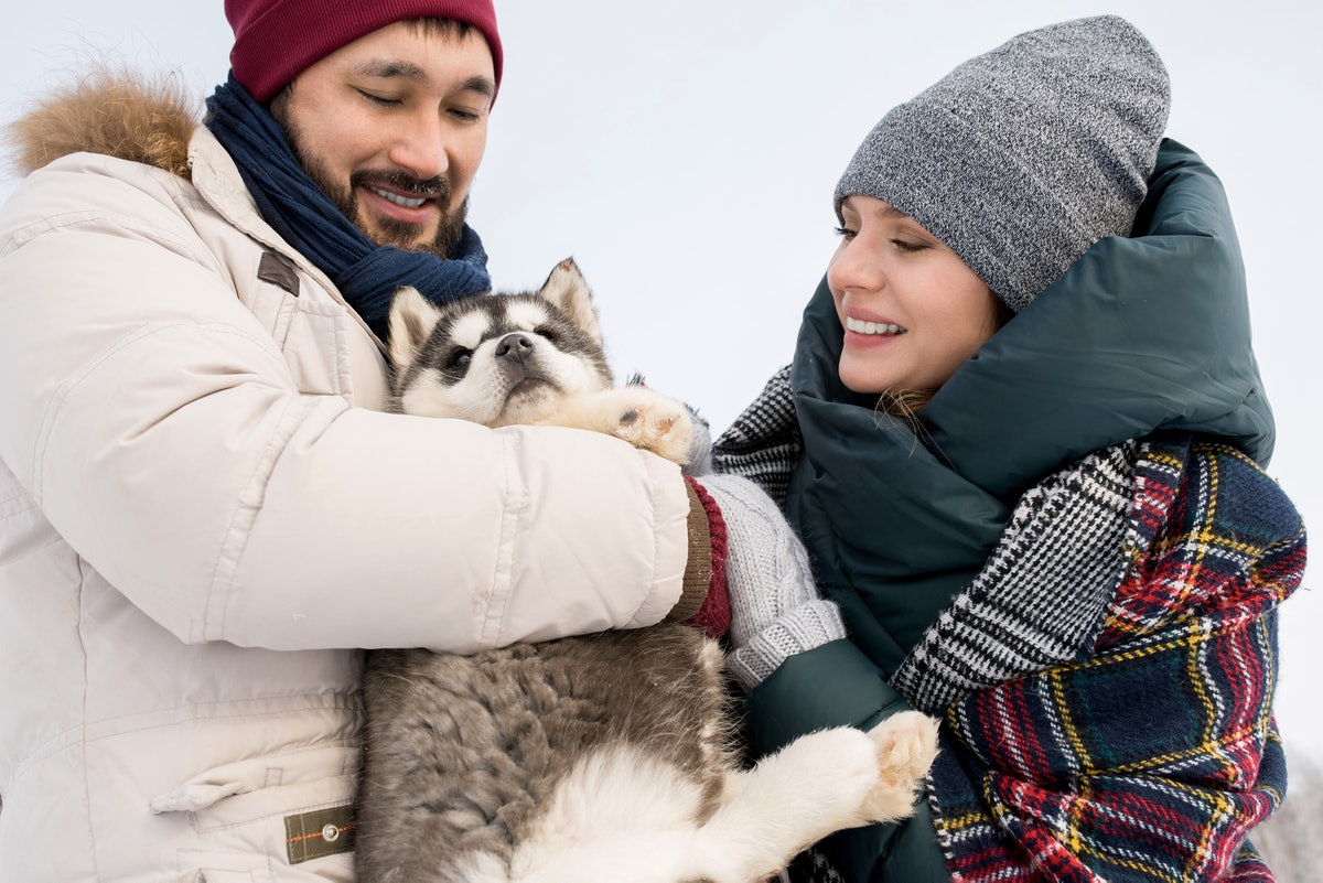 A couple who's all bundled up for the cold weather cuddles with their puppy outside.