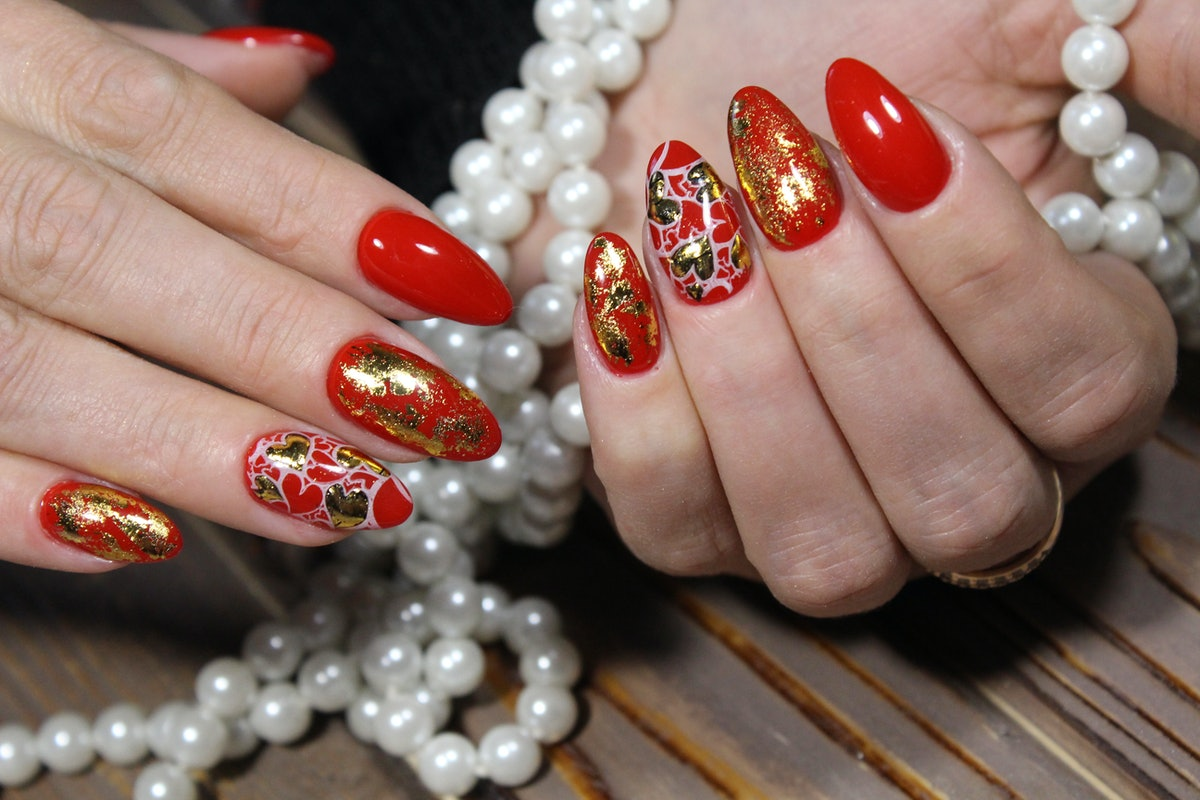 fashionable red manicure with a gold heart design
