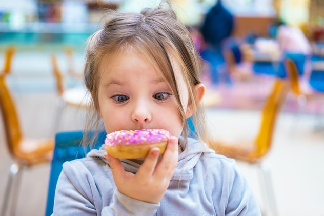 Cute girl eating a donut in a cafe. Funny portrait of a child
