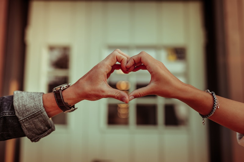 Holding hands together. Positive couple connecting fingers and creating heart shape while having house door behind