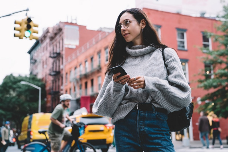Beautiful slender woman in glasses with black bag wearing denim and sweater looking away while browsing smartphone on city street