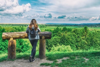 Young girl with a backpack looks at the beautiful nature. Travels. Solitude with nature. People and nature.