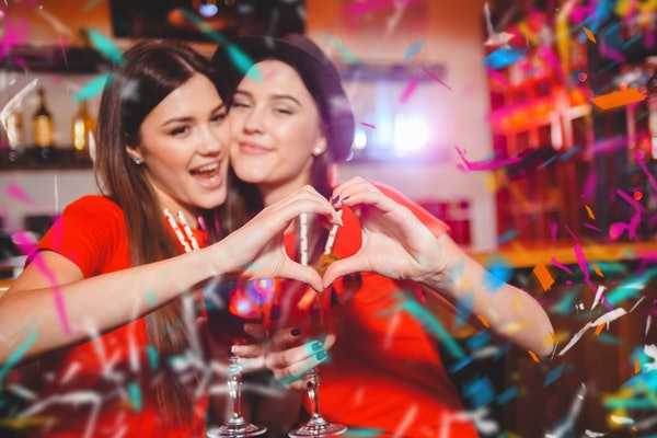 Confetti party. Two young lesbian girls make a heart with their hands at a club party.