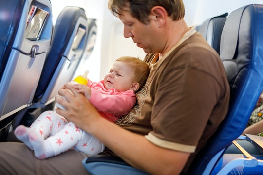 A crying baby girl and her dad on an airplane