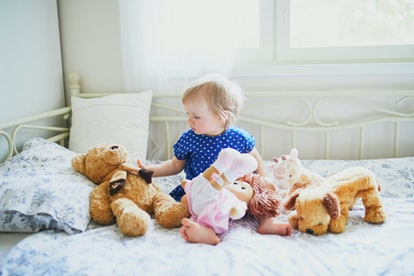 Adorable baby girl in blue dress sitting on bed and playing with doll, teddy bear and dog. Little child having fun in bedroom. Kid playing stuffed toys