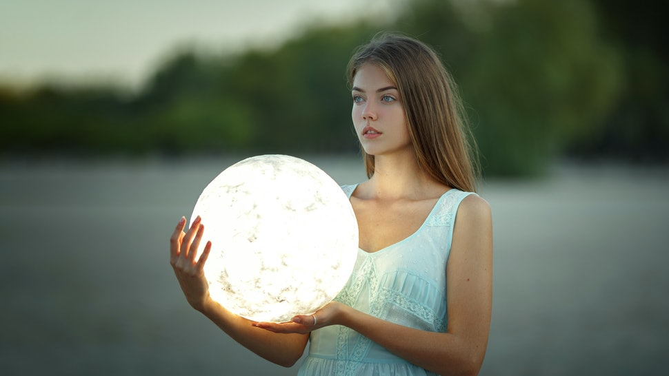 Attractive young girl in a blue dress sits on a sandy beach and holds the moon in her hands