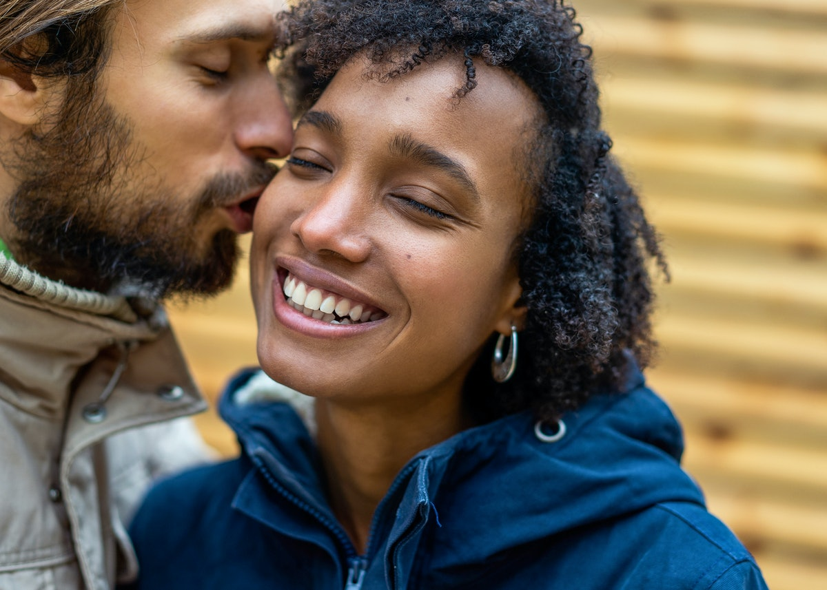 A woman closes her eyes and smiles while her boyfriend kisses her cheek.
