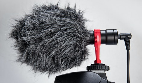 Professional Cardioid Directional Condenser Video Microphone black color attach on DSRL camera isolated on withe.