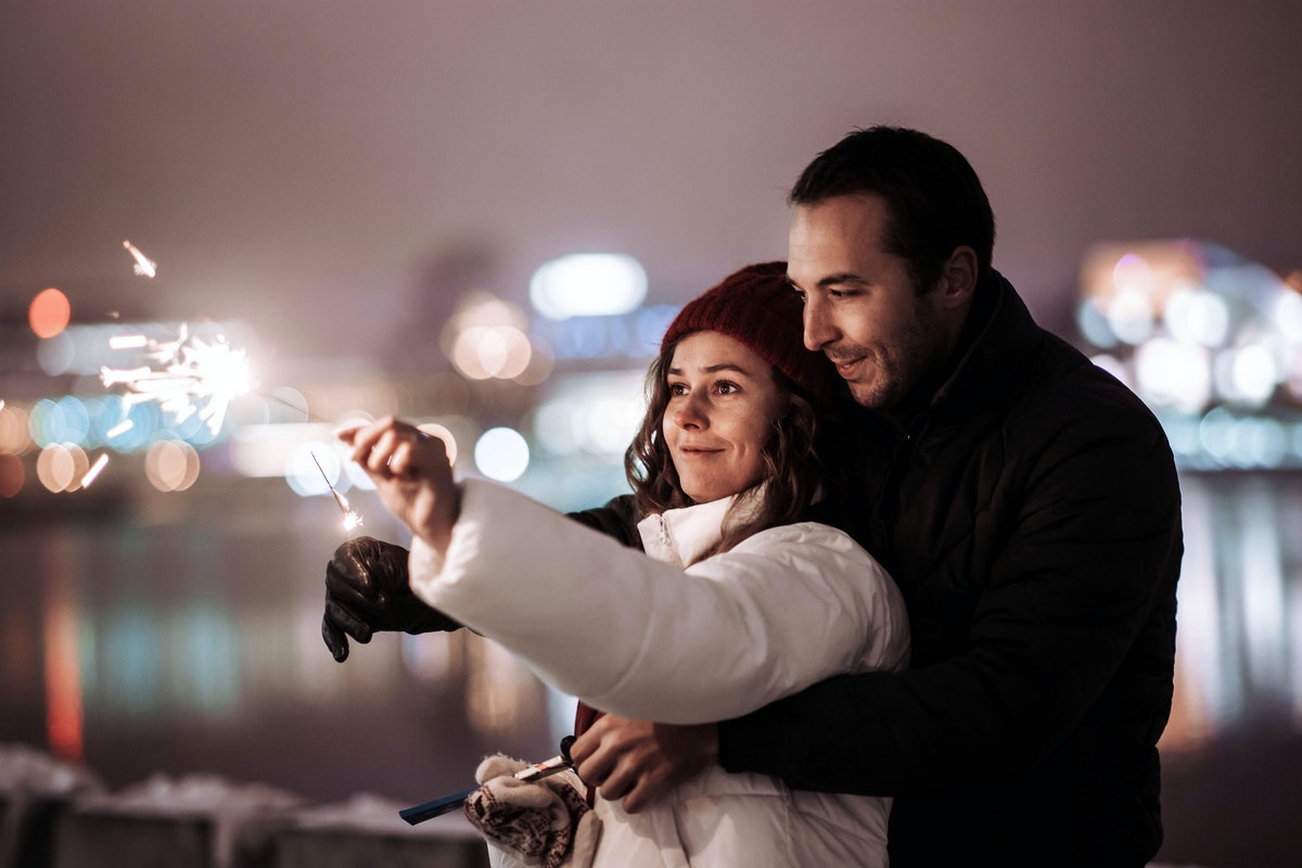 couple in love on a winter date in the city with sparklers in the evening on Christmas holidays.