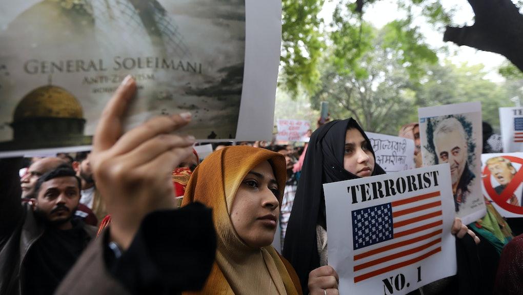 Shia Muslim community people hold portraits during the protest. Shia Muslim community people protest...
