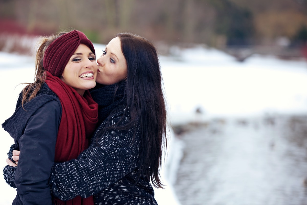 A woman hugs her girlfriend and gives her a kiss on the cheek outside in the snow.