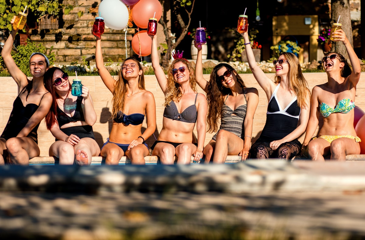 A group of friends in bathing suits holds drinks in the air while lounging poolside on a sunny day.