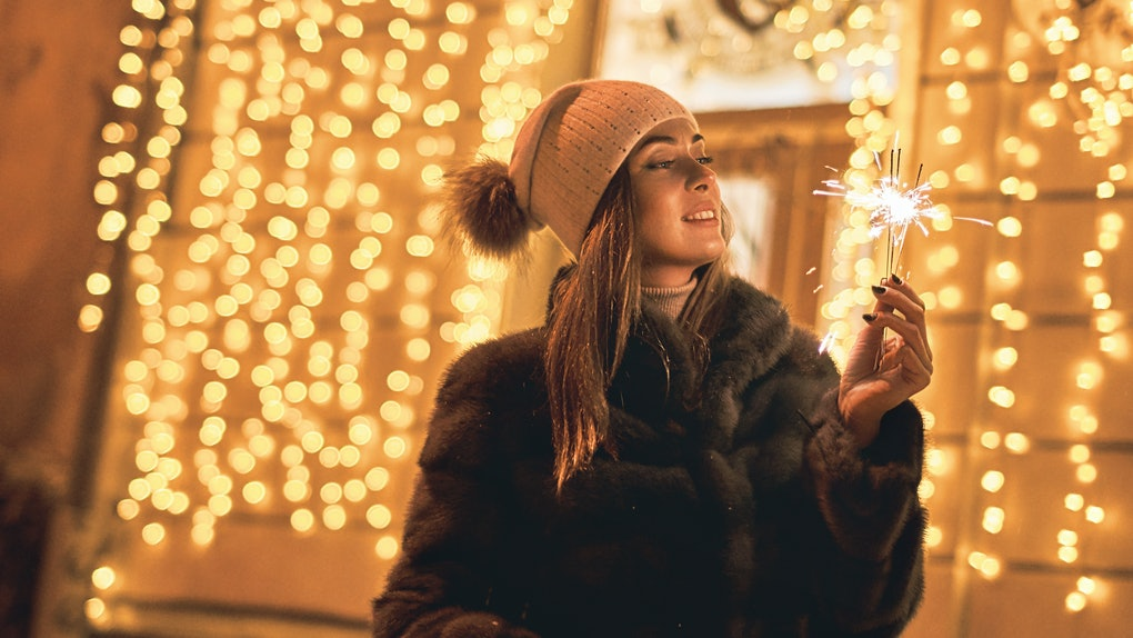 Beautiful girl holding a sparkler enjoys Christmas mood in old European city on festive golden yellow lights bokeh background
