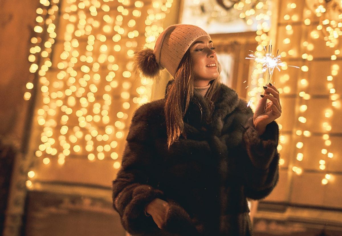 Beautiful girl holding a sparkler enjoys Christmas mood in old European city on festive golden yello...