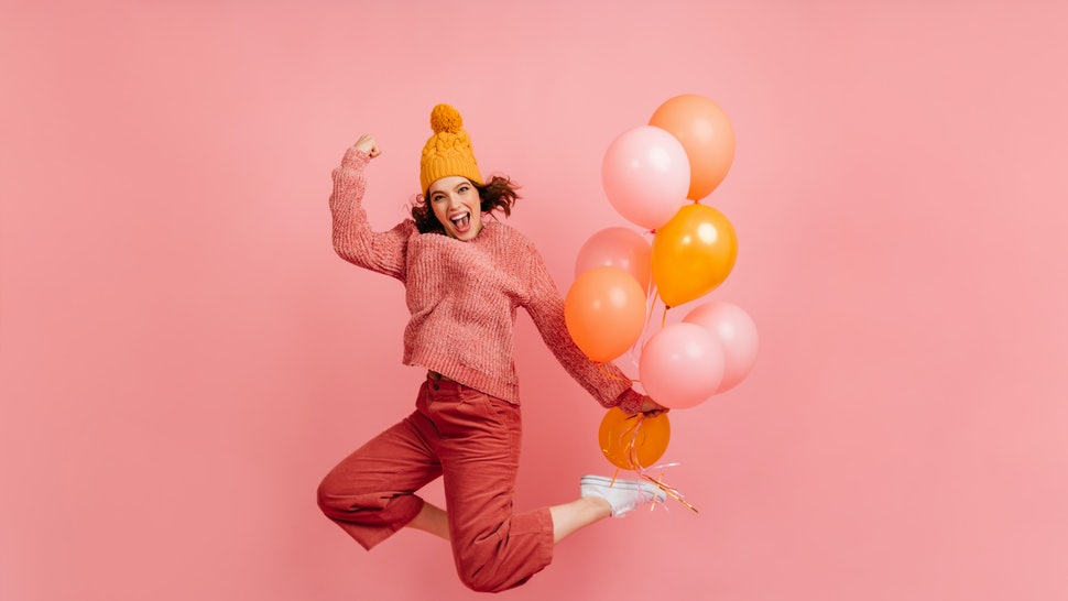 Positive girl in hat jumping and laughing. Blissful young woman dancing with party balloons.