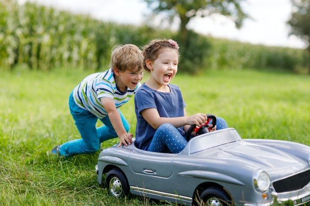 Two happy children playing with big old toy car in summer garden, outdoors. Boy driving car with lit...