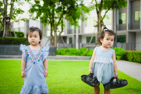 twins girl toddlers playing outside