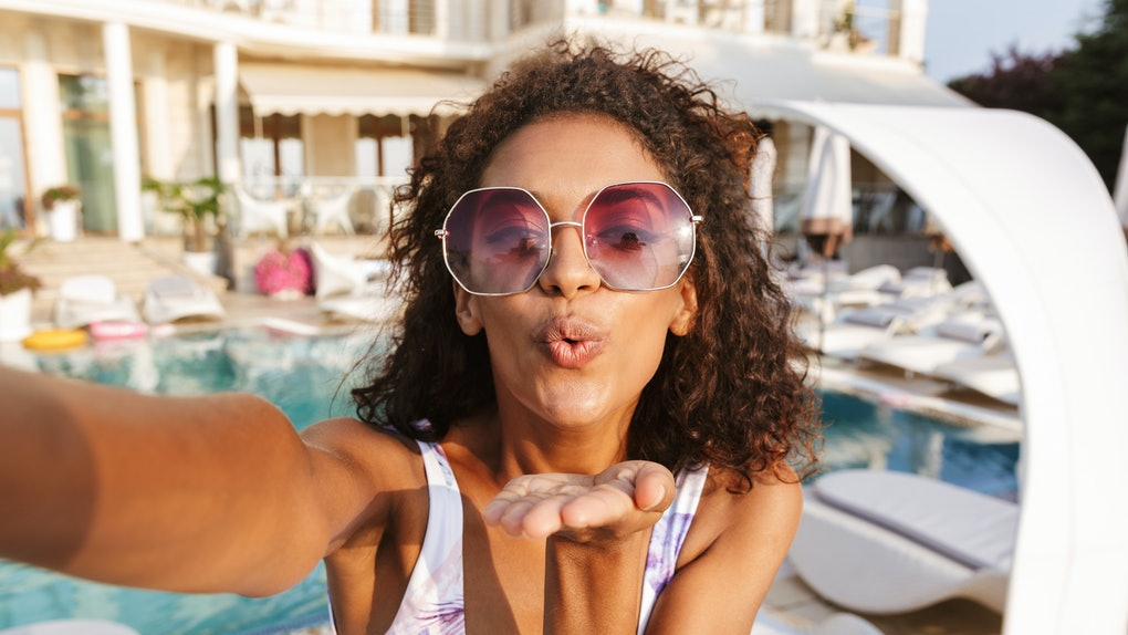 A woman wearing a swimsuit and purple sunglasses poses for a selfie poolside.