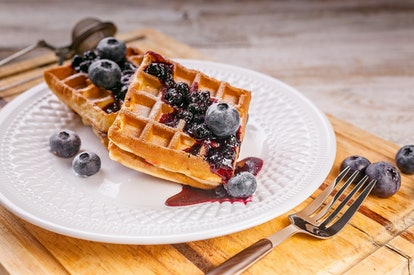 Close-up waffles with blueberries and jam. Sweet dessert. Homemade baking.