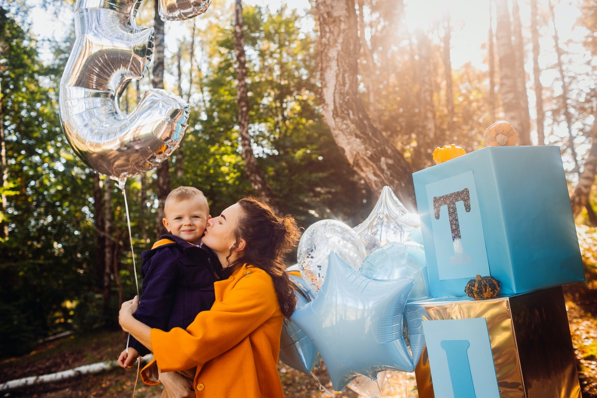 A brunette woman wearing an orange jacket kisses her nephew on the cheek for his birthday in the fall.