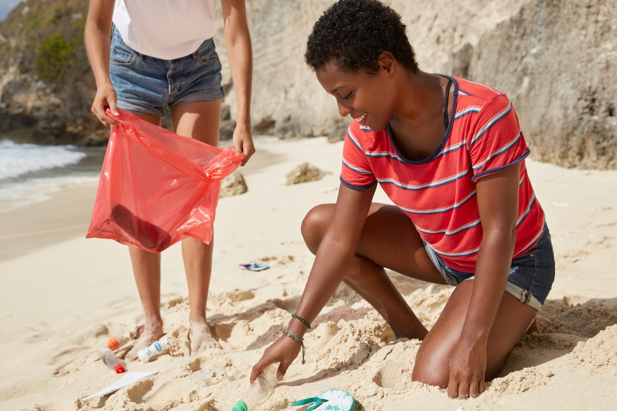 Active females clean beach from trash, care of environment, carry red litter bag, throw plastic bottles, remove bad actions of people. Planet sustainability and nature preseravation concept.