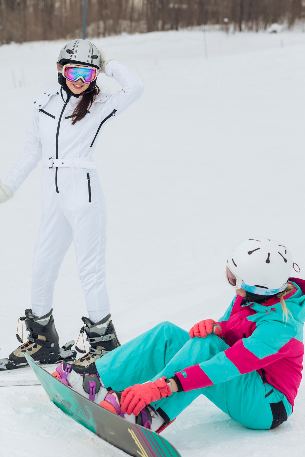 An athletic couple shares a moment while skiing and snowboarding on a snowy mountain.