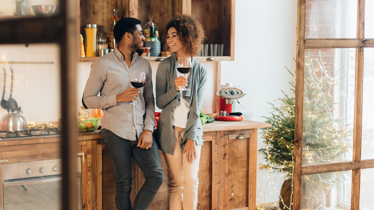A couple laughs while holding their wine glasses in the kitchen on a sunny day.