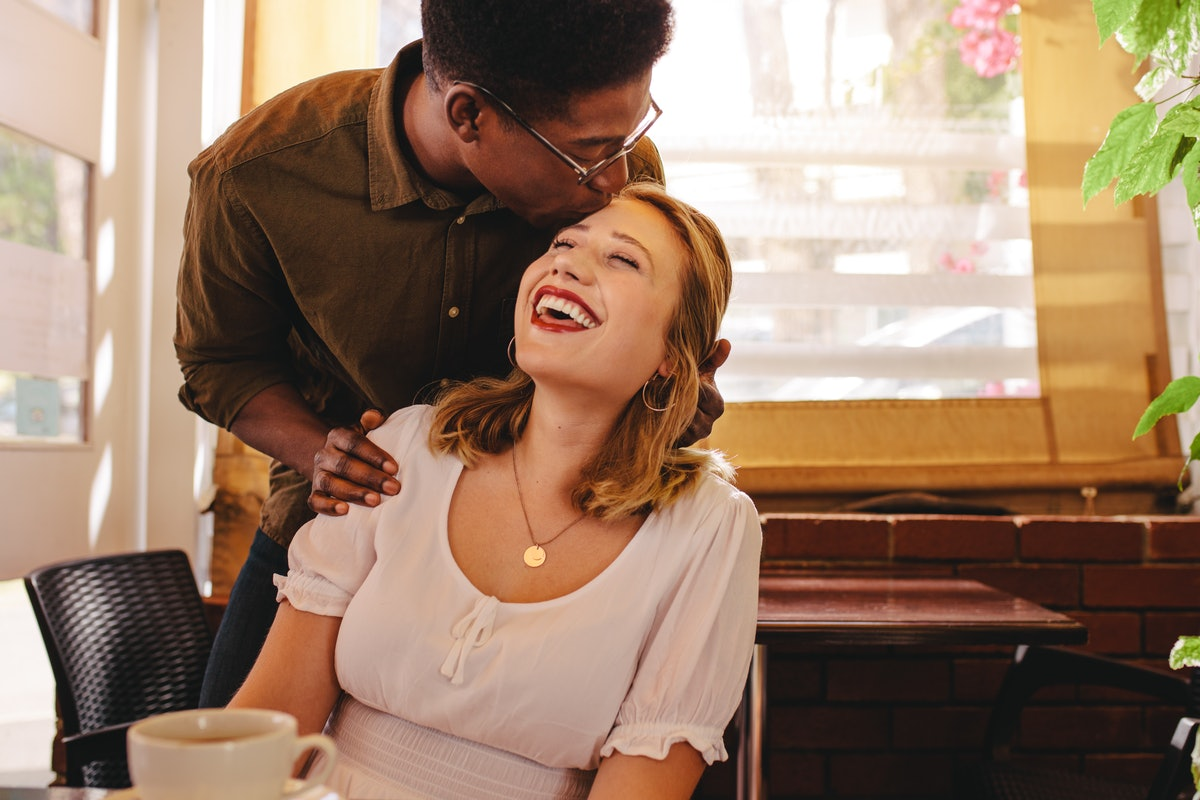 A man kisses his girlfriend on the forehead in a coffee shop.