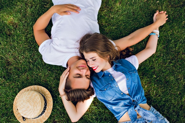 Romantic couple of young people lying on grass in park. They lay on the shoulders of each other and hold hands together. They look happy. View from above.