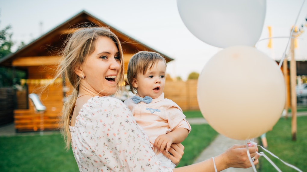 A happy blonde woman holds her nephew and some balloons for his birthday party.