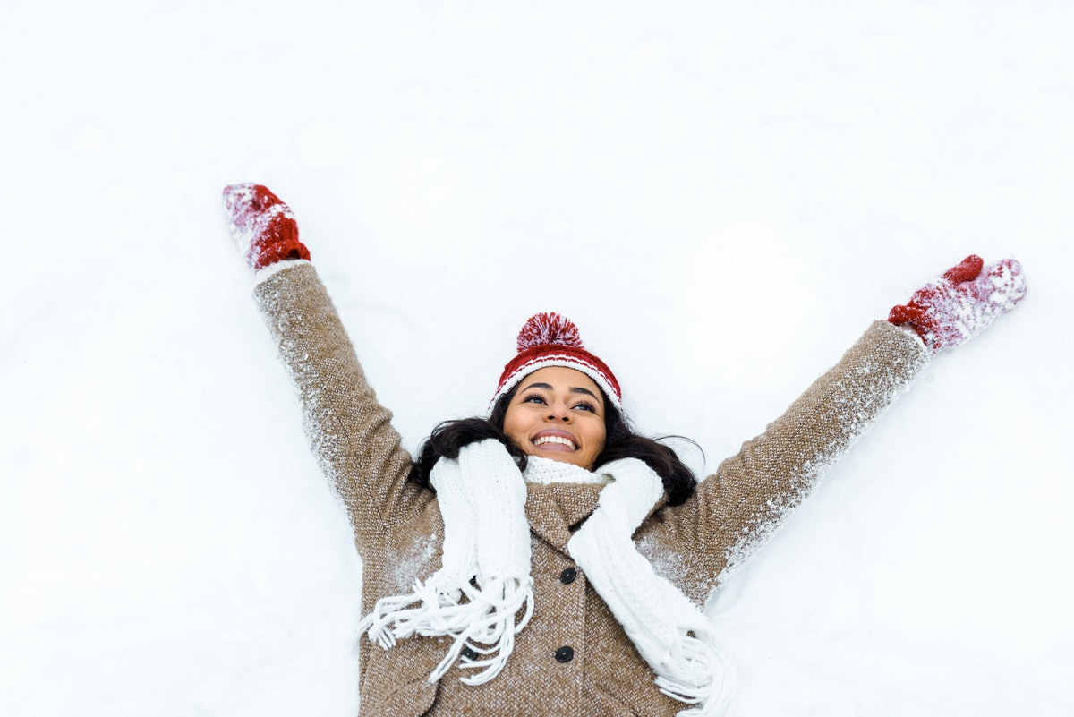 attractive african american woman doing snow angel