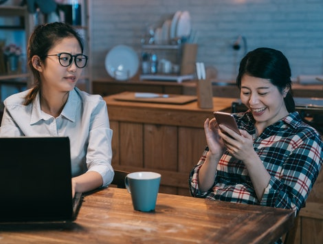 Angry business worker woman looking at lazy mate playing with the smart phone. annoyed young girl roommate friend laughing loudly sitting next to hard working employee in home kitchen.