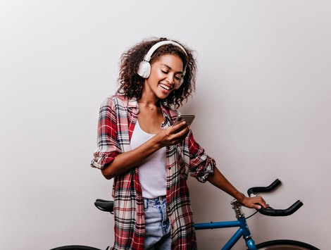 Enchanting stylish woman in headphones reading phone message. Well-dressed african girl with bicycle holding smartphone.
