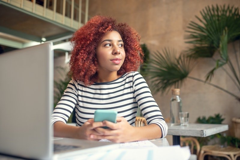 Woman holding phone. Young red-haired woman holding phone while texting her boyfriend