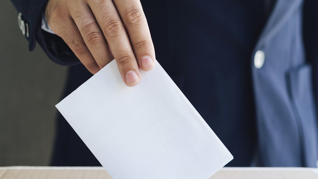 Front view man putting an empty ballot in election box