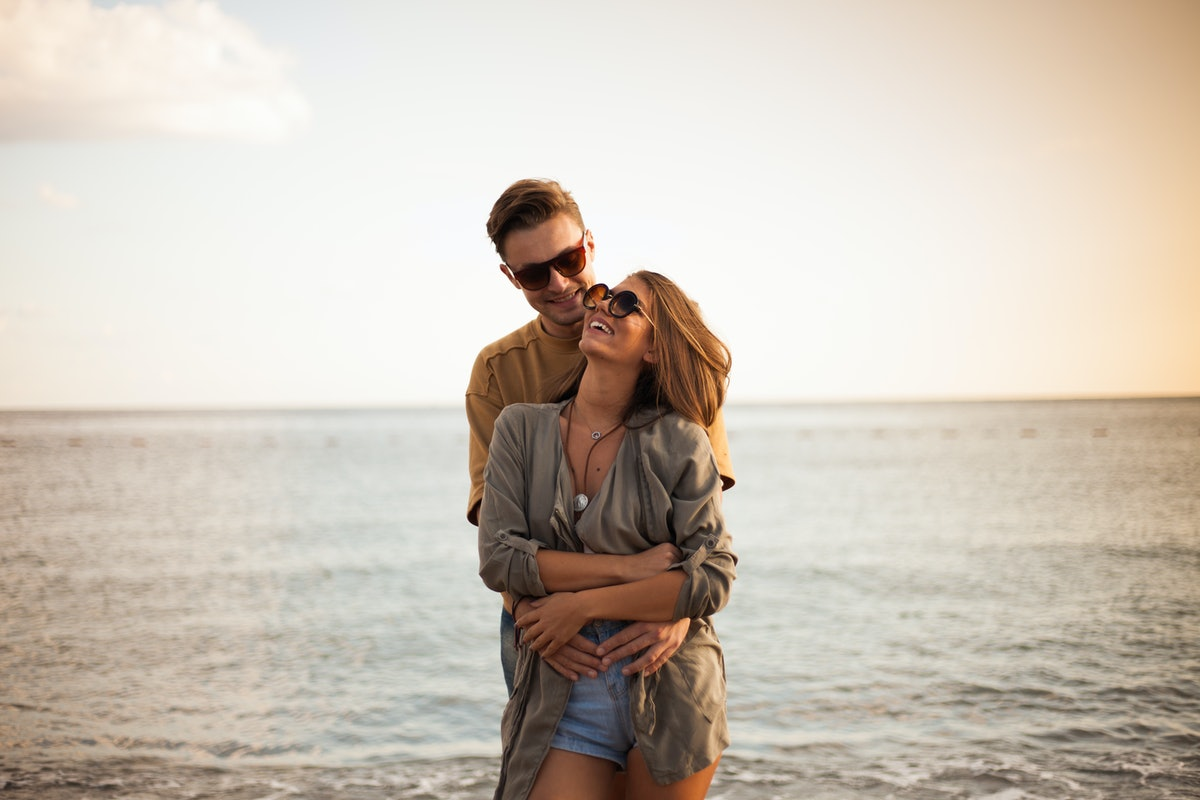 Beautiful millennial couple at the beach celebrating Valentine's Day