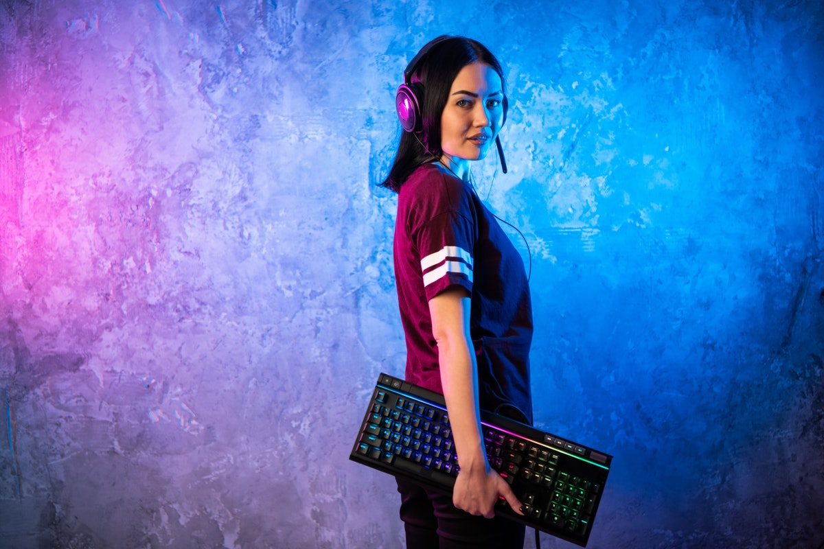 Beautiful Friendly Pro Gamer Streamer Girl Posing With a Keyboard in Her Hands, Wearing Glasses. Attractive Geek Girl with Cool Neon Retro Colors in Background.