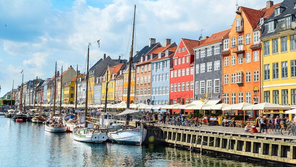 People  at sunny Nyhavn embankment with moored yachts, Copenhagen, Denmark