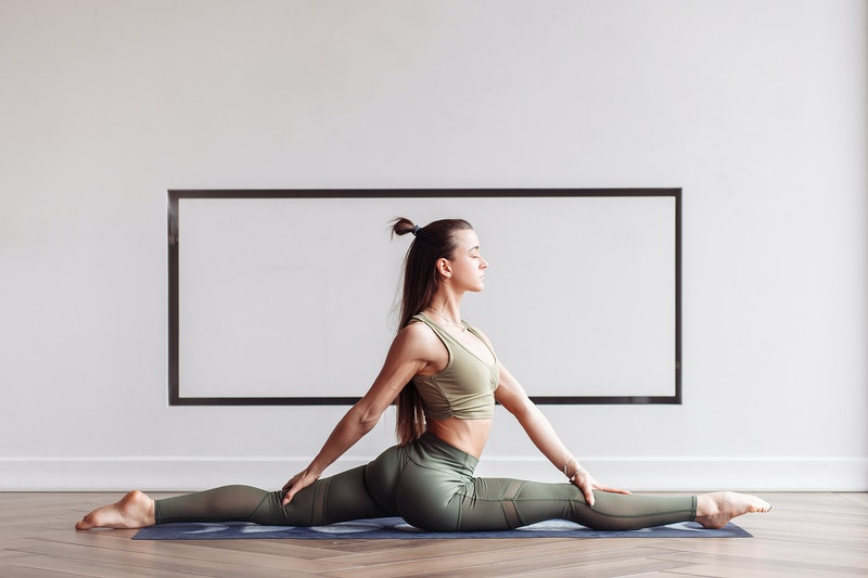 Young beautiful woman doing splits sitting on the floor on the rug. Concept of home workouts and regular classes. Advertising space