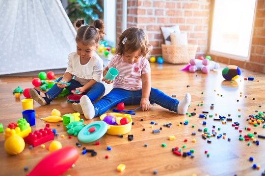 toddler girls playing with toys on the floor